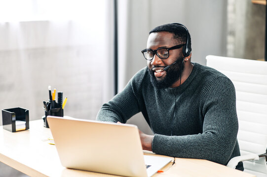 Young African-American guy is call center worker or support. Smart black man in eyeglasses uses a handsfree headset and laptop to talk online at his workplace