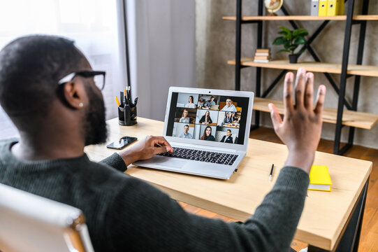 Confident African-American male worker talking online with coworkers, back view of black guy is waving hello to many people on video screen. Remote work, virtual meeting