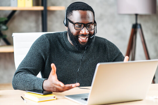 Smiling African-American guy uses a handsfree headset to talk online at his workplace, black confident man in glasses sits at the office desk and looks at laptop screen