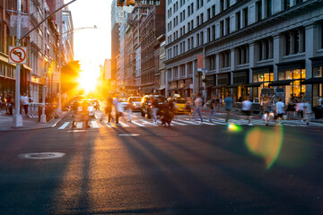 Fotomurales - Bright light of sunset shines on the crowds of people crossing a busy intersection on 5th Avenue in Manhattan New York City