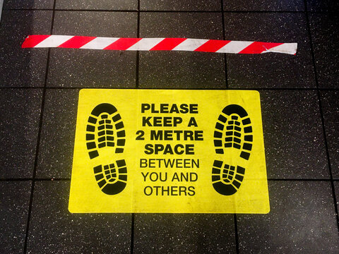 A floor sign with black lettering on yellow background says 'Please keep a 2 metre space between you and others'' Two foot prints can be seen. Red and white hazard tape makes a line.Image
