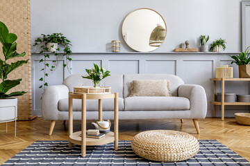 Scandinavian living room interior with design grey sofa, wooden coffee table, tropical plants, shelf, mirror, furniture, plaid pillow, teapot, book and elegant personal accessories in home decor.