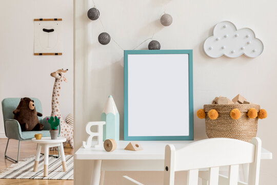 Modern and design scandinavian interior of kidroom with white desk, armachirs, mock up poster frame, natural basket, teddy bear, plush toys and cute children's accessories.