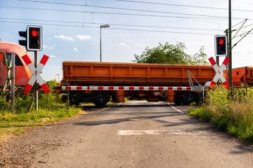 Closed barrier at a railway crossing with red warning lights on, a blurred locomotive in motion is pushing wagons.