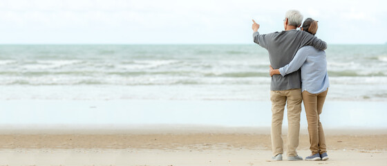 Asian Lifestyle senior couple hug and pointing on the beach happy in love romantic and relax time.