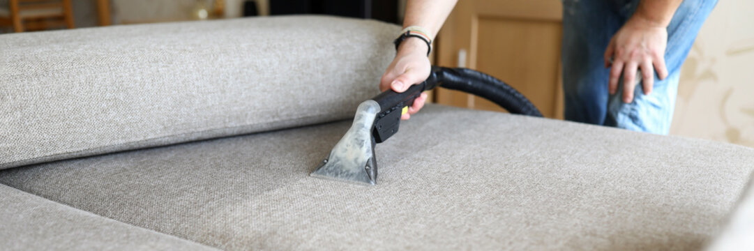 Hoovering sofa with vapor cleaning service at home