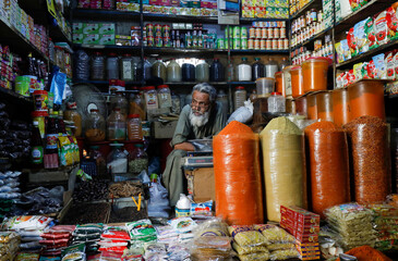 A shopkeeper waits for customers while selling spices and groceries items at the retail market, in Karachi