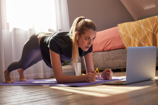 Young woman taking part in online fitness class