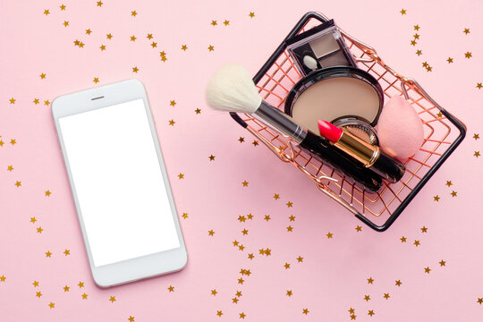 Buying beauty products online concept. Shopping basket with makeup cosmetics and mobile phone with blank white screen mockup on pink background. Flat lay, top view.