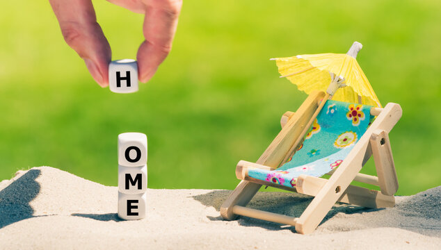 """Symbol for holidays during the corona crisis. Dice form the word """"home"""" next to a beach chair."""