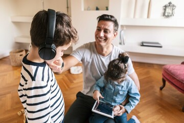 Smiling father looking at affectionate son while daughter using digital tablet at home