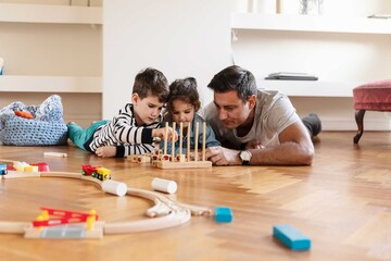 Children playing with toy block while lying down with father on hardwood floor
