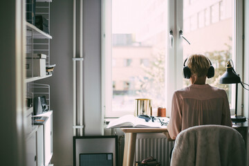 Rear view of woman in office at home sitting at desk