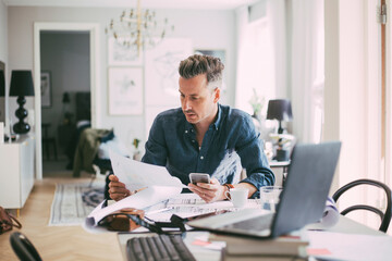 Male architect sitting at workplace reading blueprint at home