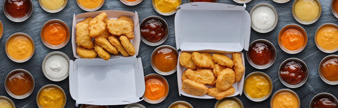 two boxes of fast food fried chicken nuggets with different dipping sauces