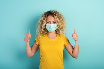 Girl is optimistic about the defeat of covid 19 coronavirus. Cyan background