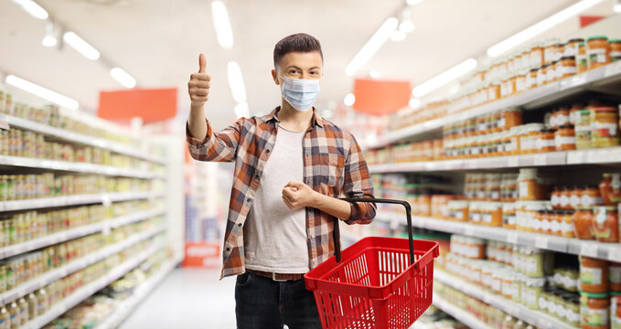 Guy in a supermarket with a protective mask and a shopping basket showing thumbs up