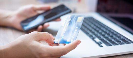 woman hand holding credit card with using smartphone and laptop for online shopping while making orders at home. business, lifestyle, technology, ecommerce, digital banking and online payment concept - fototapety na wymiar