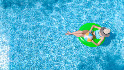 Active young girl in swimming pool aerial top view from above, child relaxes and swims on inflatable ring donut and has fun in water on family vacation, tropical holiday resort
