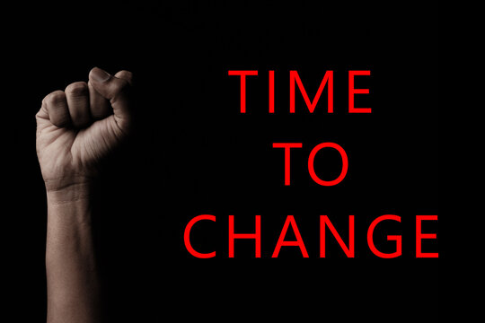 Concept against racism or racial discrimination by showing with hand gestures fist with Time to change typography