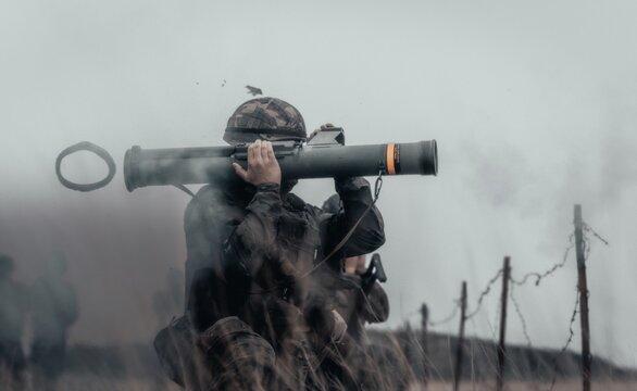 Closeup shot of a soldier in a field firing bazooka