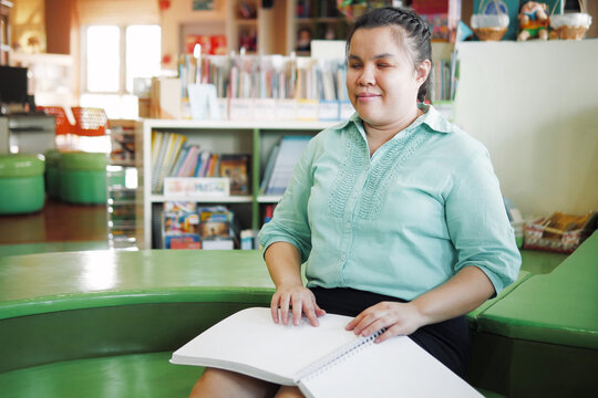 Portrait of Asian young blind person woman disabled people reading Braille book studying in creative library.