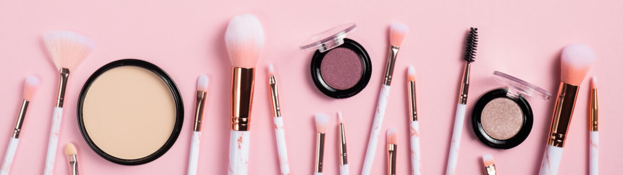 Set of makeup brushes and facial cosmetics isolated on pink background. Fashion make-up beauty products, wide banner