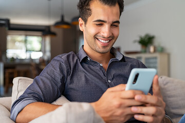 Latin man using smartphone at home