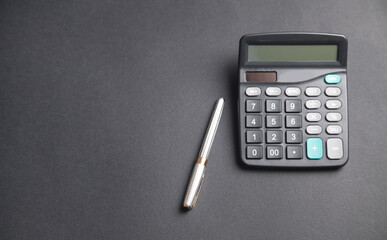 Pen and calculator on the black background.