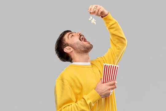 fast food people concept - young man in yellow sweatshirt eating popcorn throwing it to open mouth over grey background
