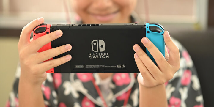 CHIANGMAI, THAILAND - 2 May 2020, Girl playing a game on Nintendo Switch console. Kid with handheld Nintendo Switch in seat home with enjoyment.