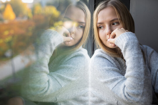 Depressed/anxious young woman sitting by a large window, feeling blue, sad, uncertain