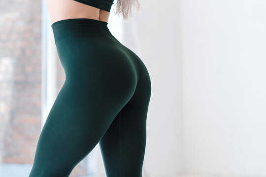 Cropped close up view photo of sexual sporty sportive tempting beautiful attractive nice round ass wearing green tight pants leggings
