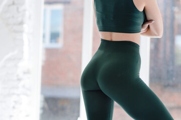 Photo sur Plexiglas Ane Close up sexy ass in tight green leggings. Athletic woman working out in a loft studio.