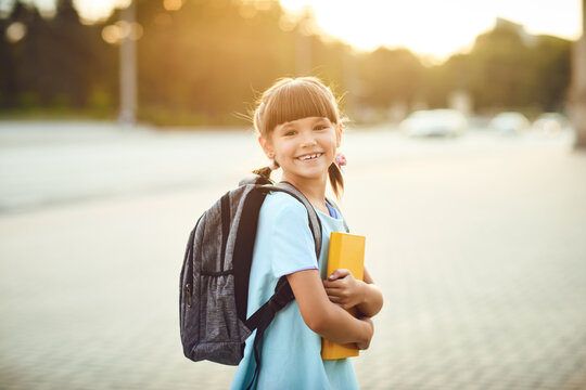 A schoolgirl with a backpack and books stands on a city street. Back to school