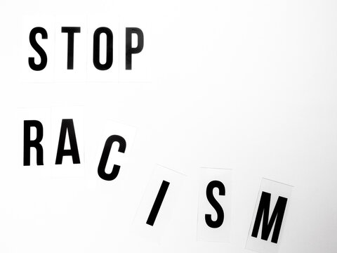 Capital letters with the text stop racism against white background