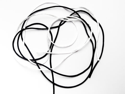 A knot with a white thread and a black thread against a white background