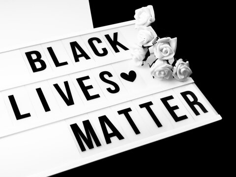 """Light box with the text """"black lives matter"""" and white roses against black and white background"""