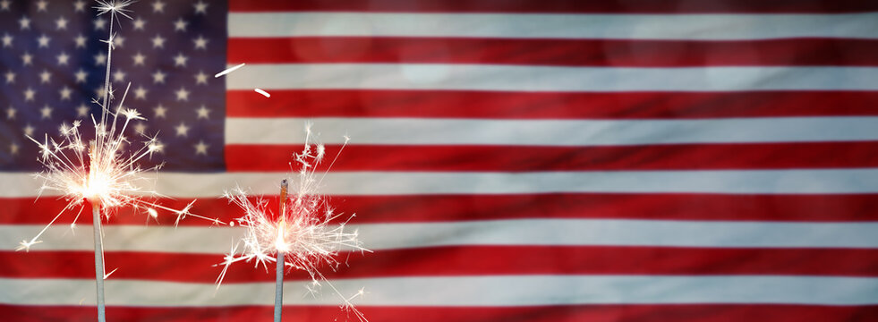 American National Holiday. US Flags with American stars, stripes and national colors. Independence Day. 4th July. Sparkler.
