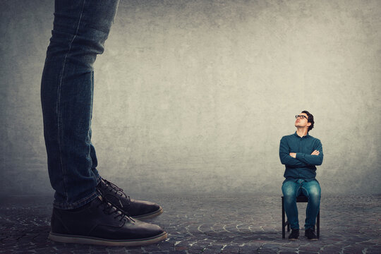 Tiny man employee seated on a chair looking up perplexed at his big boss. Office confrontation, motivation concept. Business person leadership concept.