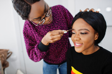 African American woman applying make-up by make-up artist at beauty saloon.