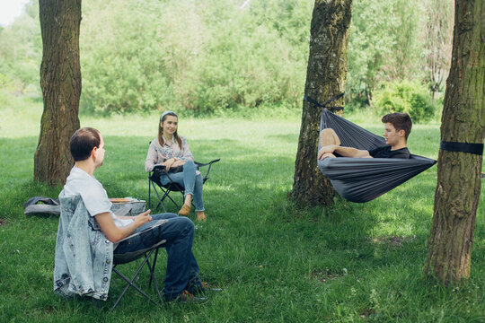 Small group of people enjoying conversation at picnic in accordance with social distancing in summer park. Friends chilling in hammock and on chairs among trees