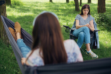 Small group of young woman enjoying conversation at picnic with social distance in summer park. Leisure activity together in new normal, safety gatherings. Social distancing