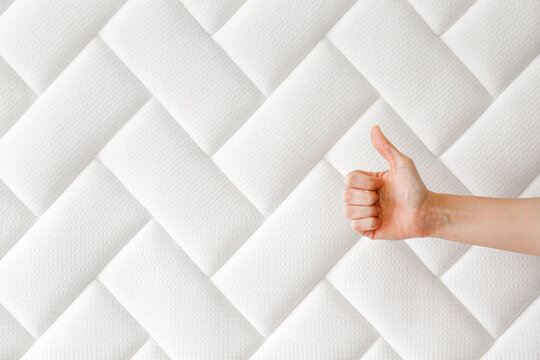 Cropped shot of woman's hand showing thumbs up over white orthopedic mattress pattern. Hypoallergenic foam matress for proper spinal alingment & pressure point relief. Background, close up, copy space