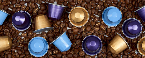 Caffeine, hot drinks and objects concept. Close up colorful capsules or pods for coffee mashine on the bed of roasted grains. Top view with space for text. Selective Focus.