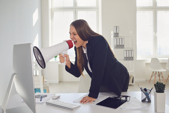 Dissatisfied businesswoman yelling via loudspeaker on computer