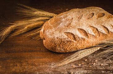 Bakery gold crusty loaf of bread on rustic wood background copy space.