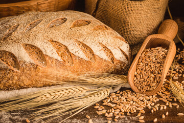 Bakery crusty loaf of bread on rustic wood background.