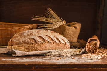 Bakery gold rustic crusty loaf of bread on rustic wood background.