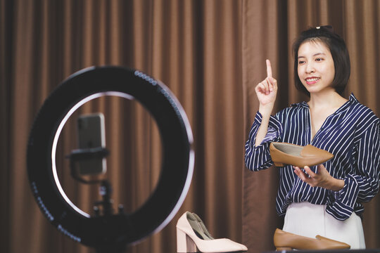Woman vlogger holding shoes in hands, looking in camera while recording video for blog.